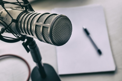 podcast equipment - microphone with pad of paper and pen