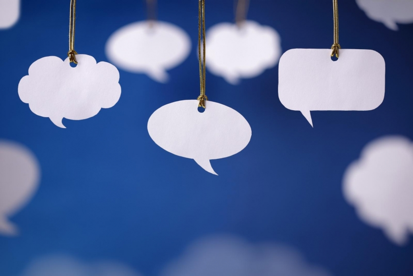 white speech and thought bubbles hanging in front of a blue background