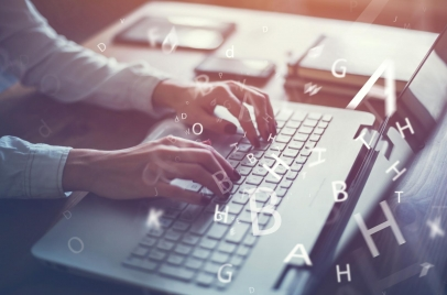 blogging concept - woman's hands typing on laptop with letters overlaid on the image