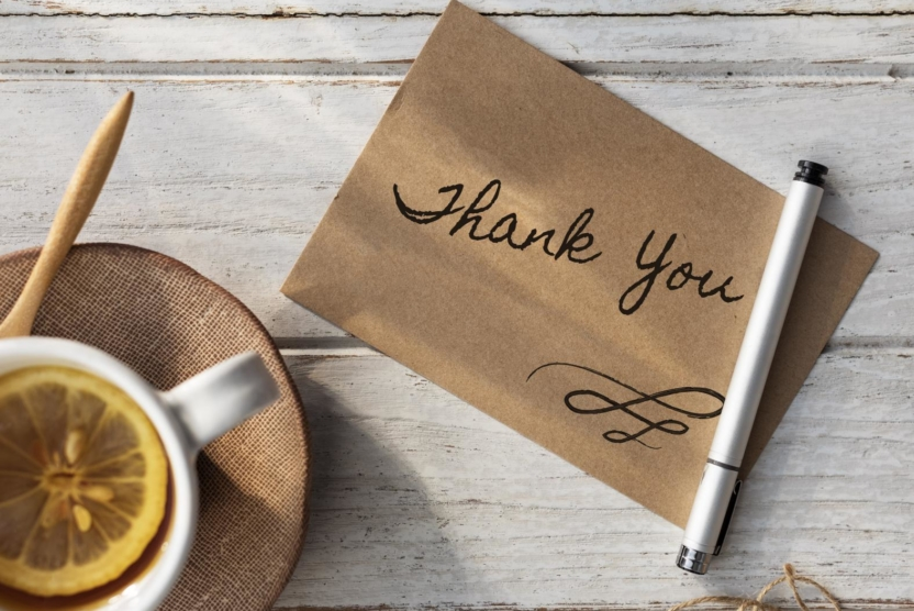 cup of lemon tea next to note with handwritten thank you