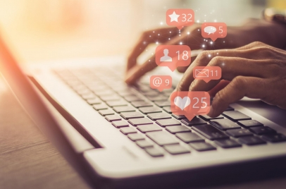 woman using laptop with social media icons above it