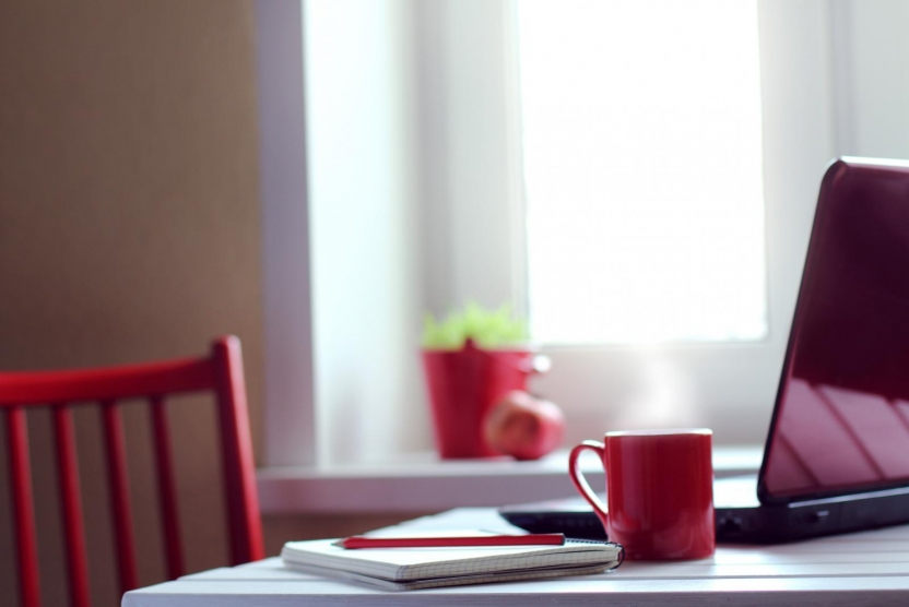 laptop, notebook, and coffee mug on a table with red chair - work from home concept