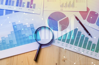 graphs and charts on a desk with a magnifying glass and a pen