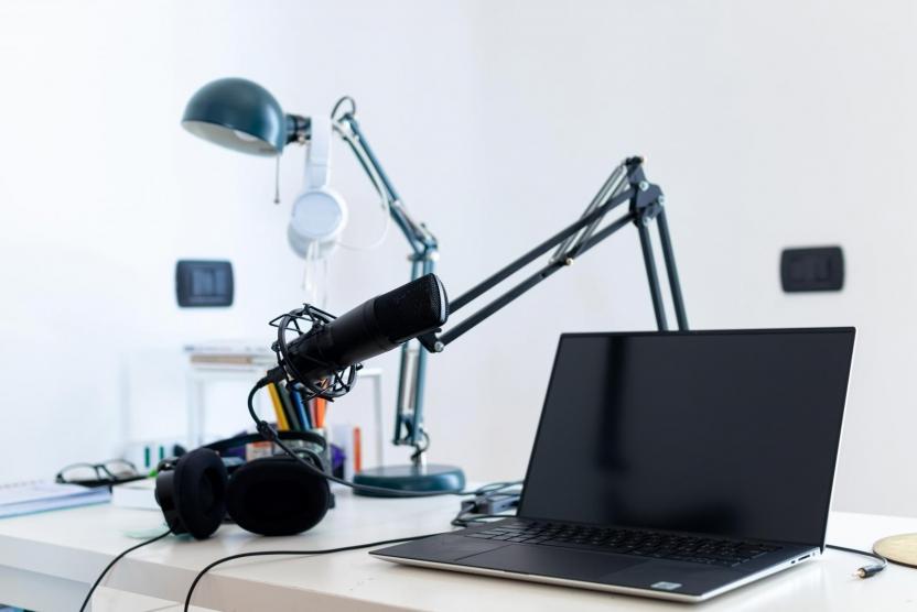 webinar equipment - headphones, microphone, laptop on a desk